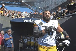 The Steelers' Alejandro Villanueva stands near the tunnel during the National Anthem Sunday at Soldier Field Chicago. His teammates stood in the background.