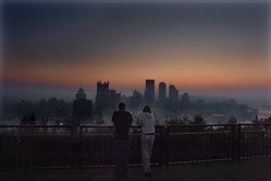 Dario Jampetro, of Moon Township, and Katie Judd, of Downtown Pittsburgh, lean on the railing and watch the red haze hang over the Pittsburgh skyline Aug. 28, 2008, while waiting for the sunrise. They had been watching the Lunar Eclipse earlier. (Darrell Sapp/Post Gazette)
