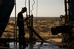 This 2014 file photo shows a worker waiting to connect a drill bit on Endeavor Energy Resources's Big Dog Drilling Rig 22 in the Permian basin outside of Midland, Texas.