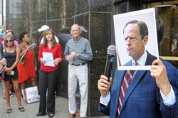 Lisa Frank, of SEIU Healthcare, holds a photograph of Sen. Pat Toomey in front her face and joined more than 100 others in a rally in support of health care outside Mr. Toomey's Downtown office on Monday.