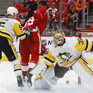 Red Wings right wing Anthony Mantha scores during a preseason game as Zach Trotman, left, and Tristan Jarry defend.