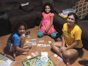 Chrystal Alexander's daughters Mya and Leyla (left and center) play the board game Life with their friend, Gabby (right) in Puerto Rico before Hurricane Maria hit.