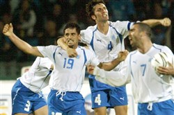 In this 2005 file photo, Israel's Abas Suan, left, and Arik Benado, center, celebrate after Suan scored during the World Cup qualifying soccer match against Ireland in Ramat Gan stadium in Tel Aviv, Israel.