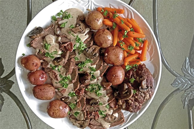 Venison with mushrooms in a sour cream gravy, plated with new potatoes and carrots