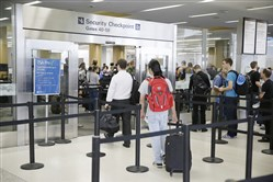 In this 2016 photo, a pair of travelers, at left, walk through a TSA Precheck security line, while other passengers wait in line to be screened, in Terminal 2 of San Francisco International Airport in San Francisco.