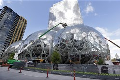 In this April 27, 2017 file photo, construction continues on three large, glass-covered domes as part of an expansion of the Amazon.com campus in downtown Seattle. Amazon said Sept. 7,  that it will spend more than $5 billion to build another headquarters in North America to house as many as 50,000 employees.