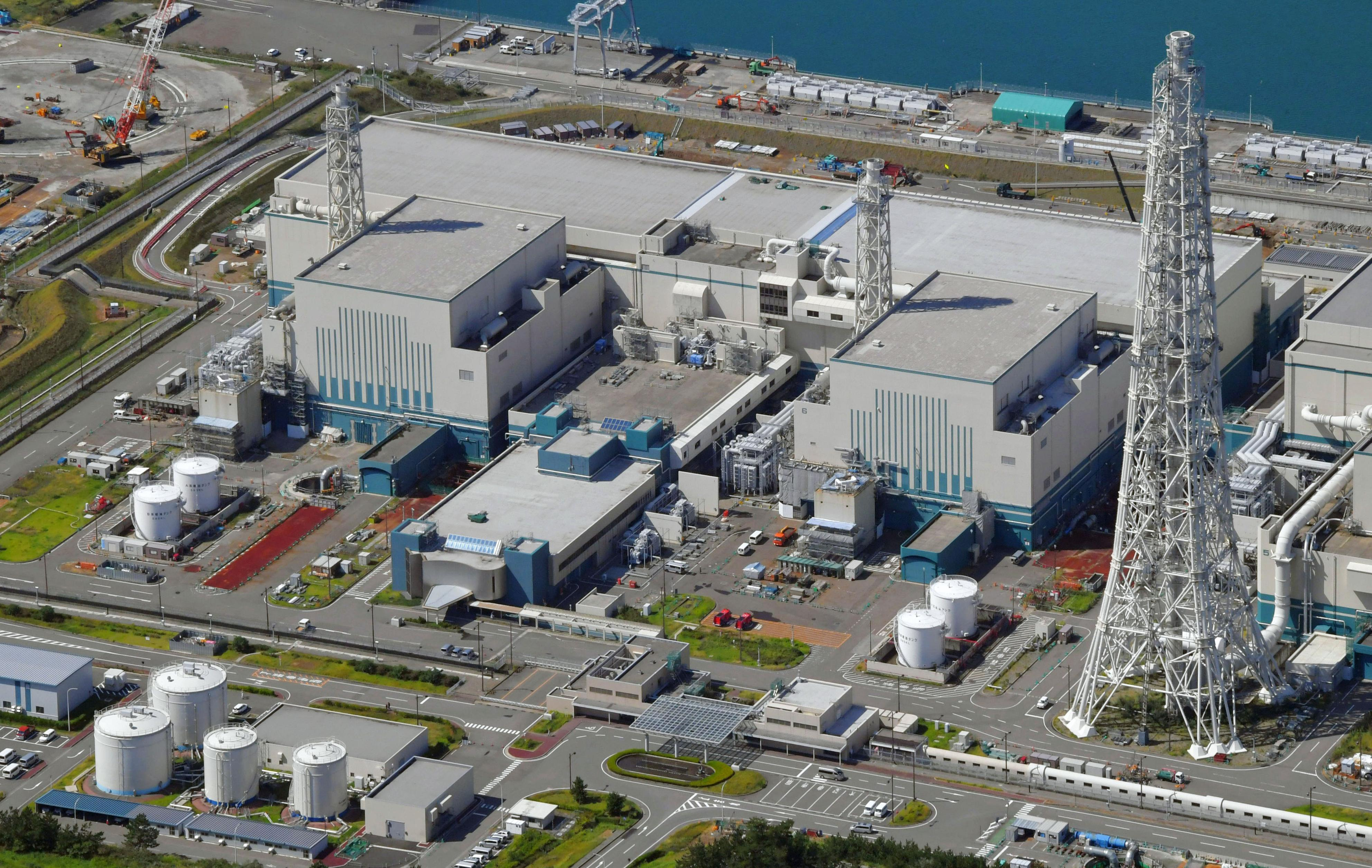 Japan Nuclear This Sept. 30, 2017 aerial photo shows the reactors of No. 6, right, and No. 7, left, at Kashiwazaki-Kariwa nuclear power plant, Niigata prefecture. Japanese nuclear regulators say two reactors run by the utility blamed in the Fukushima plant meltdowns have met their safety standards, saying the operator has since taken sufficient measures at another plant it owns. The Nuclear Regulation Authority unanimously approved Wednesday, Oct. 4, 2017, a draft certificate for No. 6 and No. 7 reactors at the plant in northern Japan operated by the Tokyo Electric Power Co. under stricter standards set after the 2011 Fukushima disaster. (Kyodo News via AP)