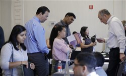 Phil Wiggett, right, a recruiter with the Silicon Valley Community Foundation, looks at a resume during a job fair in San Jose, Calif. on Aug. 24, 2017.