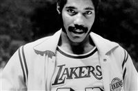 Connie Hawkins shows off his new Los Angeles Lakers uniform before start of game against the New York Knicks in Inglewood, Calif. Basketball great Connie Hawkins has died at 75.