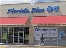 In this July 27 file photo, a person walks by a health care insurance office in Hialeah, Fla.