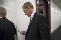 Rep. Tim Murphy, R-Pa., checks his phone as he leaves a House Republican Conference meeting at the Capitol in Washington, Wednesday. The eight-term Pennsylvania Republican announced last week that he would resign Oct. 21, 2017.