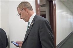 In this file photo, then-U.S. Rep. Tim Murphy checks his phone as he leaves a House Republican Conference meeting at the Capitol building in Washington, D.C., on Oct. 11, 2017.