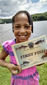 London Jackson, 9, of Braddock cups her first bluegill in her hand at Lake Arthur, Moraine State Park in Butler County.