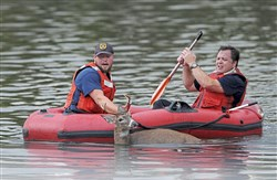 Shawn Eigenbrode, paramedic crew chief for City of Pittsburgh EMS, maneuvers the boat toward shore while Patrick Corcoran with Pittsburgh Animal Control holds onto a four-point buck that jumped into the Highland Park Reservoir Thursday, October 12, 2017 in Highland Park. (