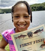 London Jackson, 9, of Braddock cups her first bluegill in her hand at Lake Arthur, Moraine State Park.