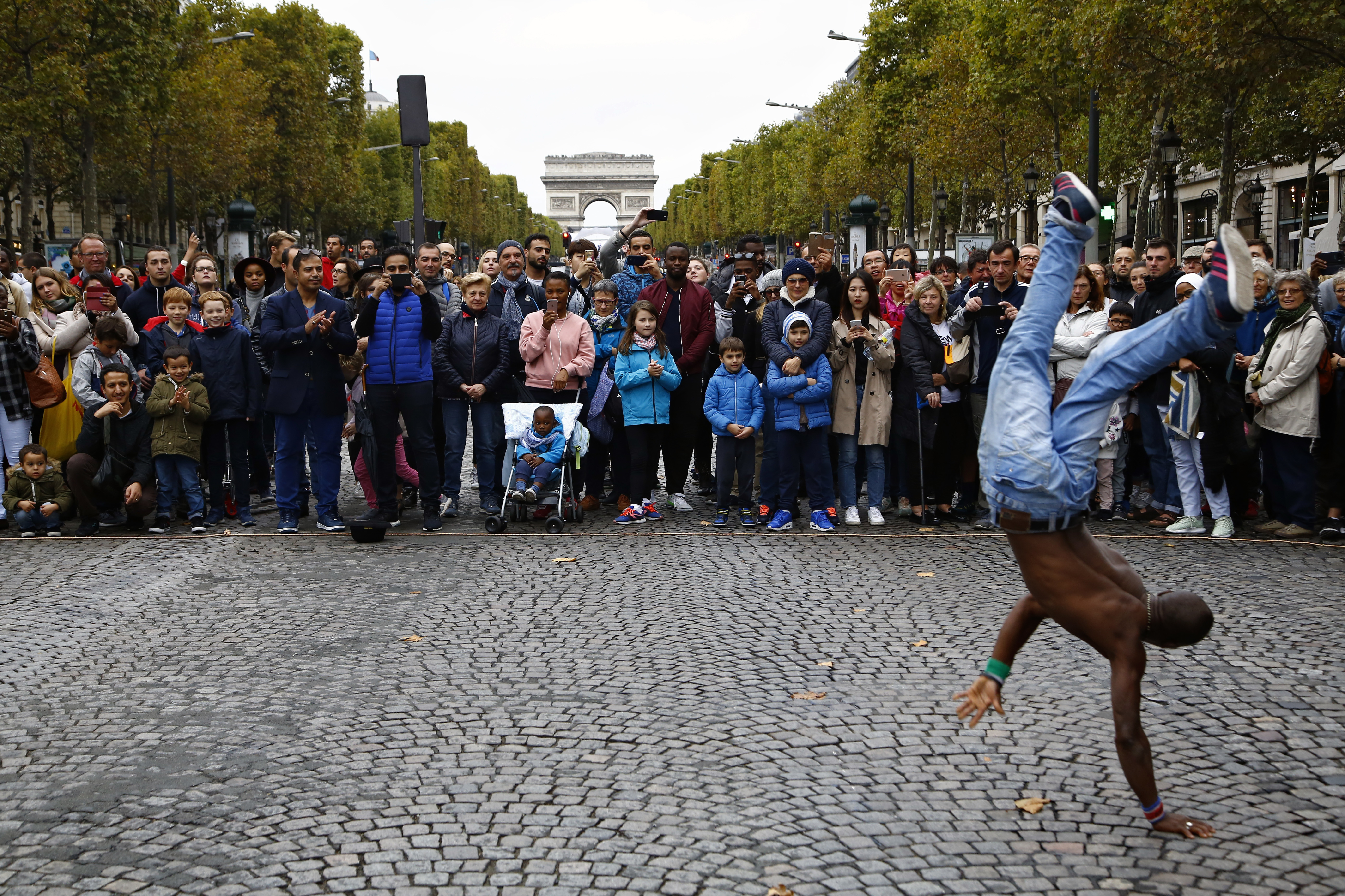 """France Banning Cars FILE - In this Oct.1 2017 file photo, people watch a dancing performance on the champs Elysees avenue during the """"day without cars"""", in Paris. In its latest initiative to reduce pollution, Paris City Hall is planning to ban gas-powered cars by 2030. The controversial move follows Mayor Anne Hidalgo's plan to ban all diesel cars from the city by 2024, when Paris will host the Summer Olympics.(AP Photo/Thiabult Camus, FILE)"""