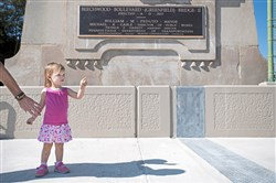 "Liviana Kozusko, 2, of Rankin points to bicyclists on the newly rebuilt Greenfield Bridge as her father Matt Kozusko reaches to hold her hand during the ""Bridge is Back"" event on Oct. 14 in Greenfield. Behind her is the newly installed plaque that commemorates the building of the new span."