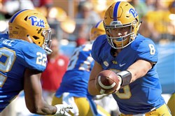 Pitt quarterback Kenny Pickett hands off to Darrin Hall against N.C. State in the third quarter Saturday, October 14, 2017 at Heinz Field.