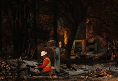 In this Oct. 14 file photo, utility workers make their way through the fire-ravaged neighborhood of Coffey Park in Santa Rosa, Calif.