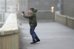 A man take selfie in the high wind at Lahinch on the west coast of Ireland Monday.