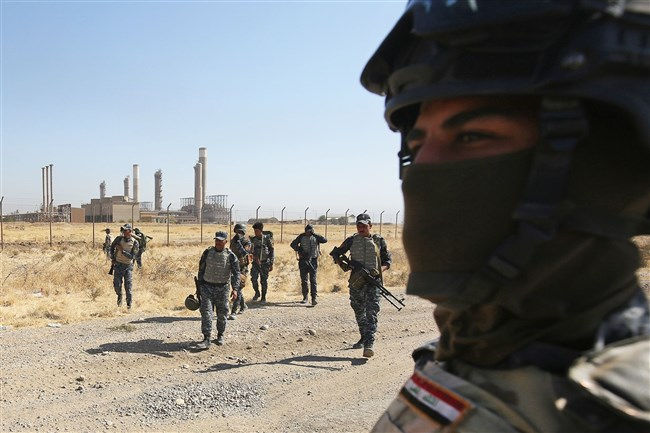 Iraqi forces walk in front of an oil production plant as they head toward the city of Kirkuk during an operation against Kurdish fighters on October 16, 2017.