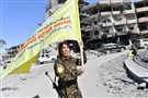Rojda Felat, a Syrian Democratic Forces (SDF) commander, waves her group's flag at the iconic Al-Naim square in Raqqa on October 17, 2017.