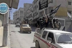 In this file photo posted April 25, 2015, on the Twitter page of Syria's al-Qaida-linked Nusra Front, Nusra Front fighters stand on their vehicles and wave their group's flags as they tour the streets of Jisr al-Shughour, Idlib province, Syria.