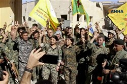 This frame grab from video released Oct. 17, 2017, and provided by Hawar News Agency, a Syrian Kurdish activist-run media group, shows fighters from the U.S.-backed Syrian Democratic Forces celebrating their victory in Raqqa, Syria.