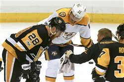 Nashville's Scott Hartnell watches as a trainer tends to Ian Cole after he took a puck to the face Oct. 7