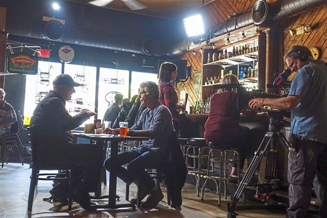 """Anthony Bourdain, center, has a beer with author Stuart O' Nan at the Squirrel Hill Cafe while filming a segment for his CNN show, """"Parts Unknown."""""""