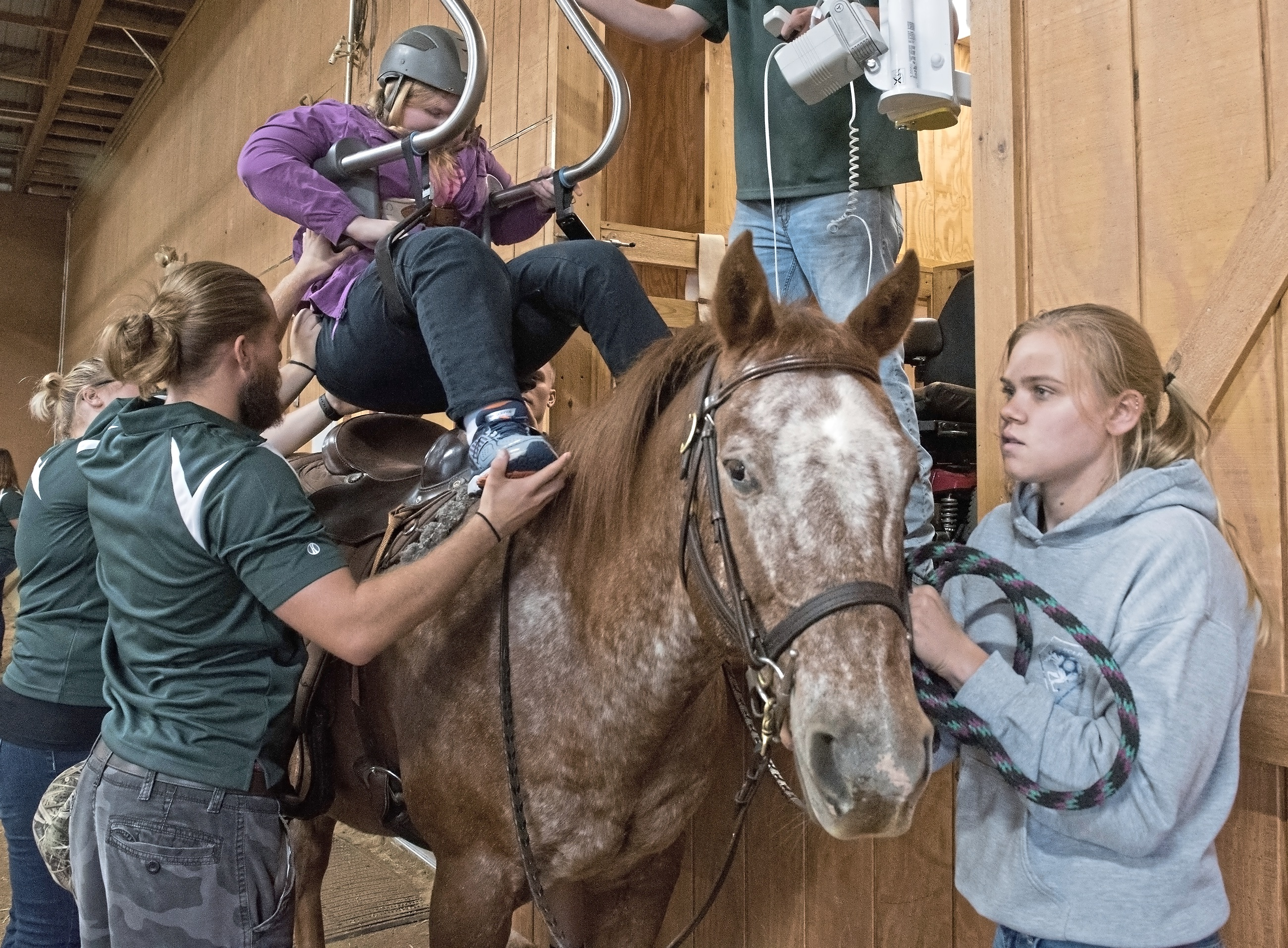 20171006hnRiding-3-4 Kimberly Weibman of Avalon is lowered onto Harley, a 21-year-old Appaloosa, at Storm Harbor Equestrian Center in Slippery Rock.