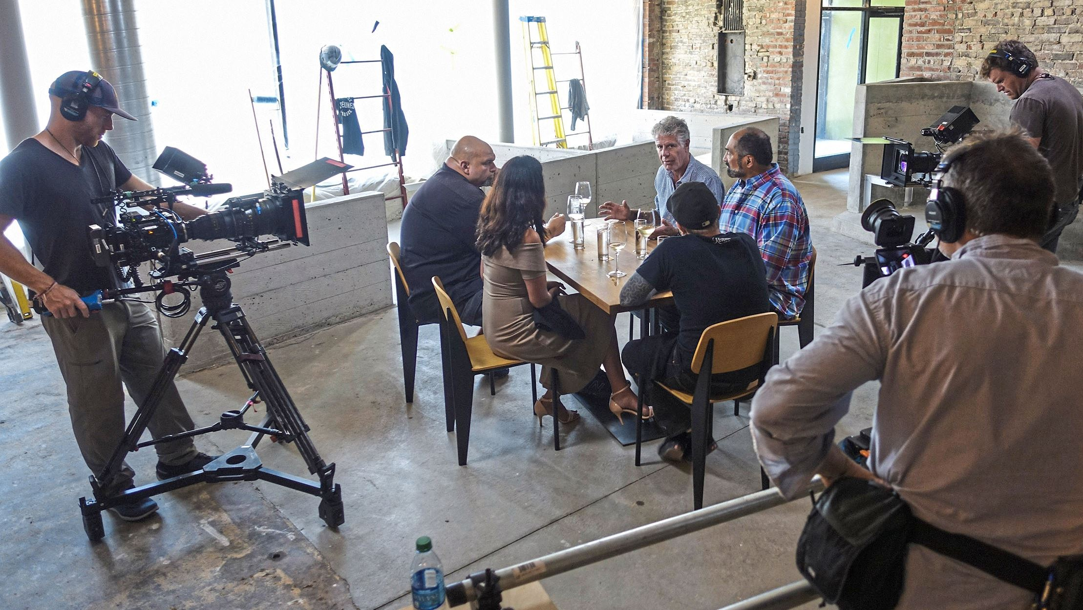"""bourdain 1Pittsburgh The """"Parts Unknown"""" crew films Anthony Bourdain at the yet-to-be-opened Superior Motors in Braddock. From left: Braddock Mayor John Fetterman, his wife Gisele Fetterman, Superior Motors' owner and chef Kevin Sousa and Steelers great Franco Harris."""