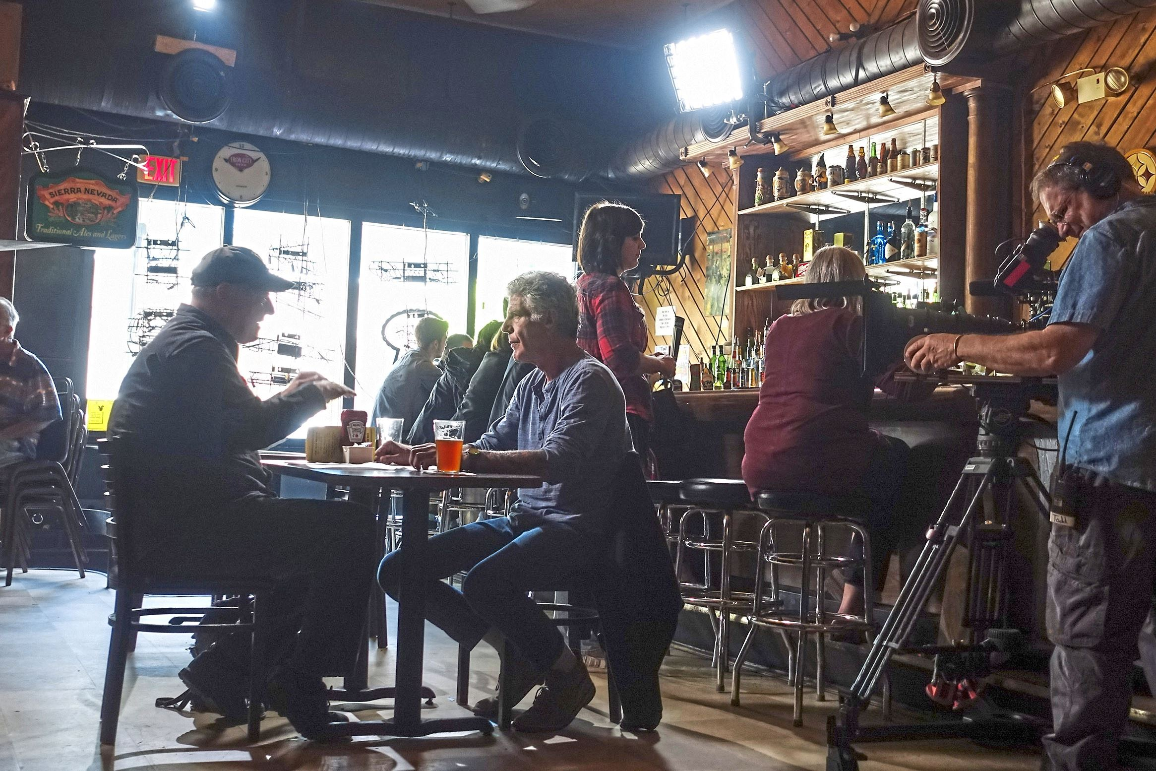 """bourdain pittsburgh squirrel-3 Anthony Bourdain, center, has a beer with author Stewart O' Nan at the Squirrel Hill Cafe while filming a segment for his CNN show, """"Parts Unknown."""""""