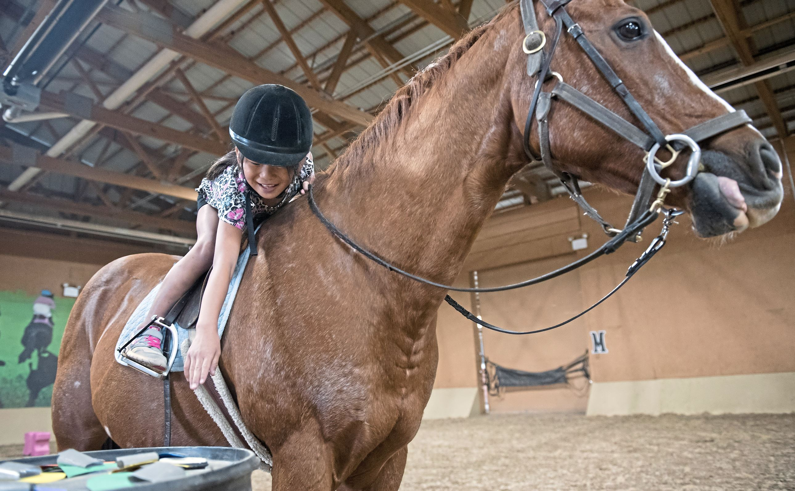 20171006hnRiding-9-10 Heather Holtz, 8, of Slippery Rock reaches for a paper shape during a riding lesson at Storm Harbor Equestrian Center in Slippery Rock.