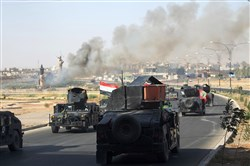 In this October 16, 2017, file photo, smoke billows as Iraqi forces advance toward the center of Kirkuk during an operation against Kurdish fighters.