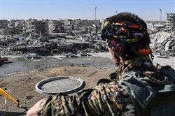 A member of the Syrian Democratic Forces (SDF) stands at a position overlooking the iconic Al-Naim square in Raqqa on October 18, 2017.