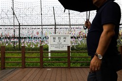 A visitor holding an umbrella walks past a barbed-wire fence at the Imjingak pavilion near the Demilitarized Zone in Paju, South Korea.