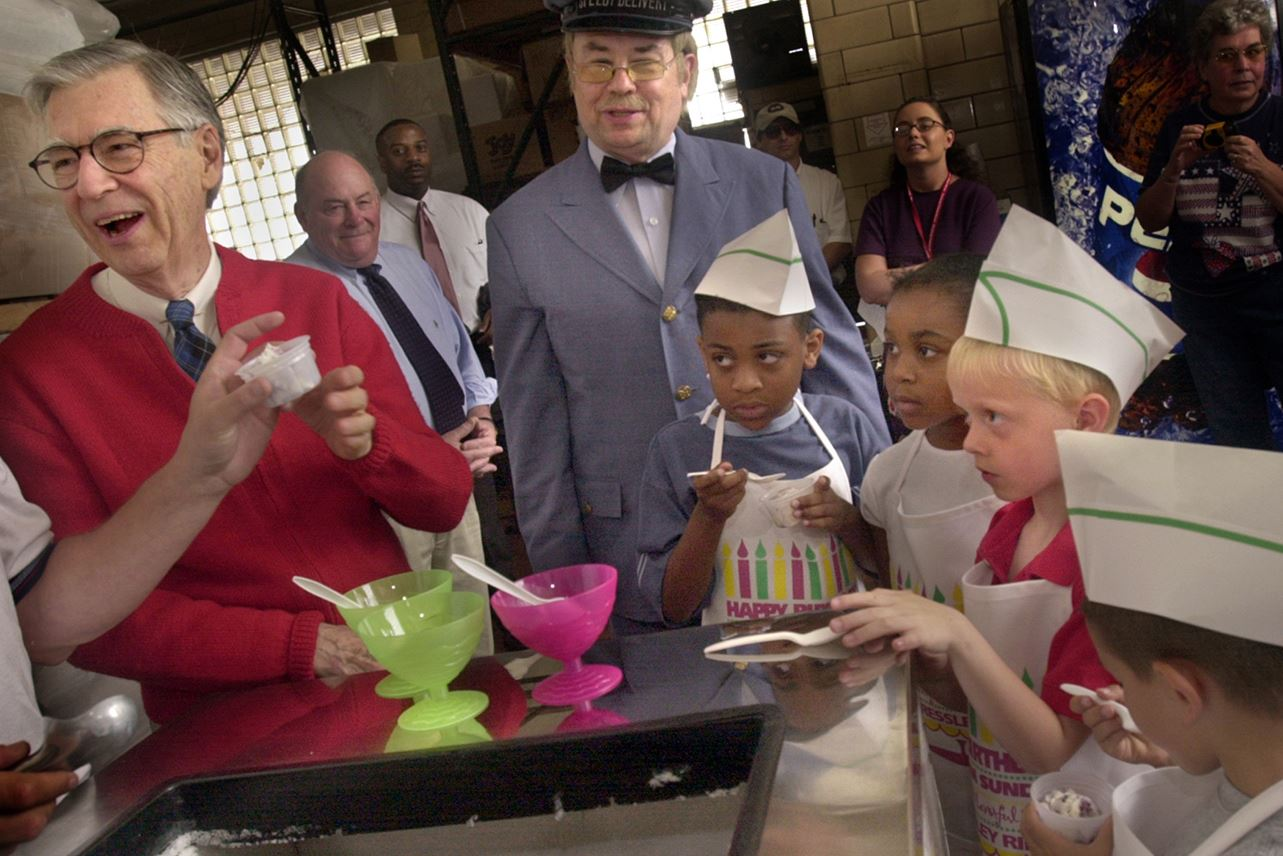 """NS_MRROGERS6CC00KB2-4 This June 2002 photo shows Fred Rogers picks """"Blueberry-Go-Round"""" as his favorite new ice cream made by Reinhold's dictated by Mister Rogers ingredients for the 10th annual Presley Ridge Ice Cream Sunday. Also on hand is Mr. McFeely (David Newell), left to right, and children from Presley Ridge School, Ira Johnson,8 and his sister Nicole Johnson, 7, Zachary Weaver, 6, and Eddie Scott, 7."""