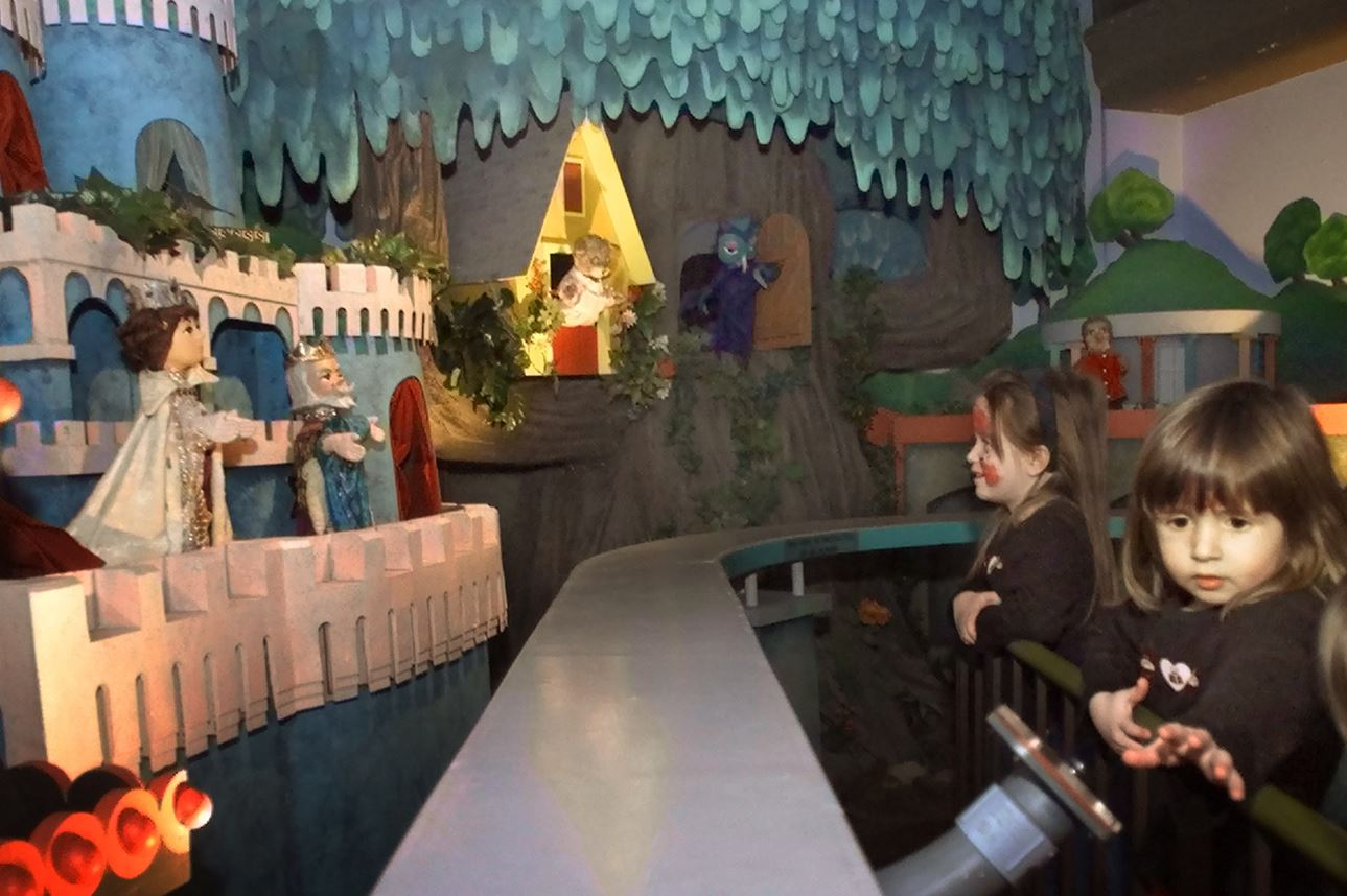 NS_MRROGERS5XZ00KD7-3 Emme Germanos, 2, at right, reaches for the start button while her four-year-old sister Arielle watches the puppett characters from the Mr. Rogers' Neighborhood display at the Children's Museum in Pittsburgh on Jan. 17, 2001.