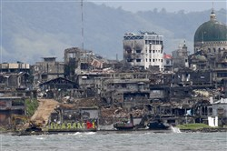 "Armored Personnel Carriers are positioned near the bullet-riddled ""I Love Marawi"" landmark sign, center, at the ""Main Battle Area"" where pro-Islamic State militants are making a final stand amid a massive military offensive of Marawi in the southern Philippines on Oct. 19, 2017."
