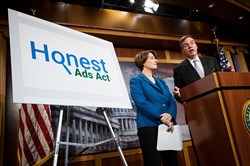 "Left to right, Sen. Amy Klobuchar, D-Minn., looks on as Sen. Mark Warner, D-Va., speaks during a press conference to introduce the ""Honest Ads Act"" on Capitol Hill in Washington on October 19, 2017."