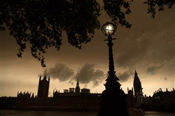 In this October 16, 2017, file photo, a street lamp is lit opposite the Houses of Parliament during a reddish sky caused by remnants of Hurricane Ophelia dragging in dust from the Sahara Desert in London.