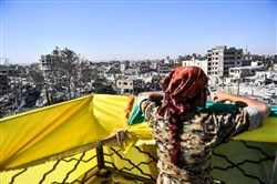 A female fighter of the Syrian Democratic Forces looks on during celebrations at the iconic Al-Naim square in Raqqa on October 19, 2017, after retaking the city from Islamic State fighters.