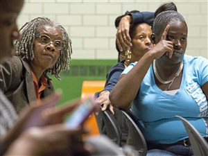 Antonisha Vaughn, right, of Homewood, listens to Pittsburgh Councilman Ricky Burgess speak during a community meeting Thursday at the Community Empowerment Association in Homewood. More than 100 East End residents are poised to be relocated due to what HUD says are poor housing conditions at the Bethesda-Homewood Properties.