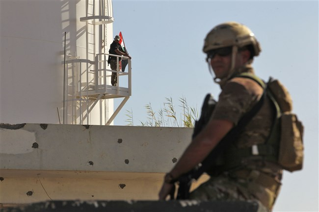 A member of the Iraqi government forces' stands guard at a humvee turret as another raises the Iraqi national flag from an oil silo at the Bai Hassan oil field, west of the multiethnic northern Iraqi city of Kirkuk, on October 19, 2017.