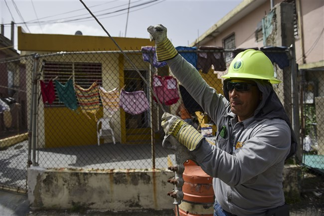 In this Oct. 19, 2017, photo, Ezequiel Rivera works with the Electric Energy Authority to restore distribution lines damaged by Hurricane Maria in the Cantera community of San Juan, Puerto Rico.