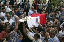 People carry the coffin, covered with the an Egyptian flag, of police captain Ahmed Fayez who was killed in a gun battle in al-Wahat al-Bahriya area in Giza province, about 135 kilometers (84 miles) southwest of Cairo, during his funeral at Al-Hosary mosque, in Cairo, Egypt, Saturday, Oct. 21, 2017.