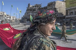 Fighters from the Women's Protection Units, or YPJ, hold a celebration Thursday in Paradise Square in Raqqa, Syria.