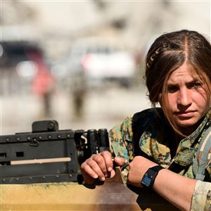 In this October 19, 2017, file photo, a female fighter of the Syrian Democratic Forces sits on the top of an armored vehicle in Raqqa.
