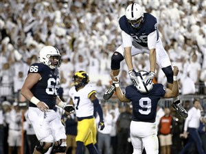 Penn State's Mike Gesicki celebrates by jumping over quarterback Trace McSorley after McSorley scored a touchdown against Michigan during the first half in State College, Pa., Saturday, Oct. 21, 2017.